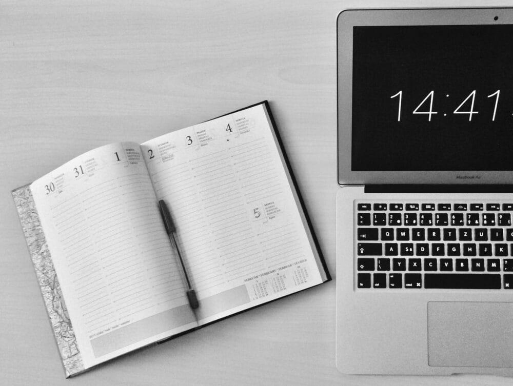 Un agenda ouvert à côté d'un ordinateur portable