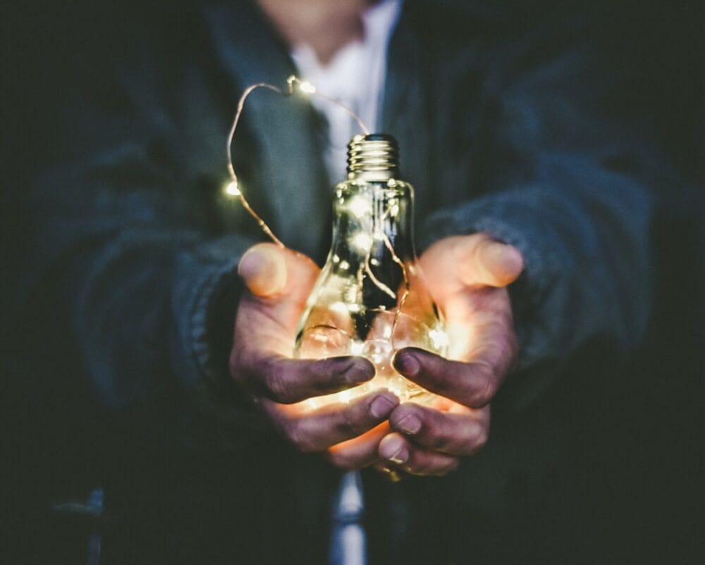 Un professionnel qui tient une ampoule allumée dans ses mains